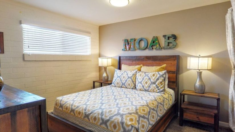 "Bed with colorful yellow and gray bedspread with the words ""MOAB"" in block letters written above it with an exposed brick wall painted white to one side."