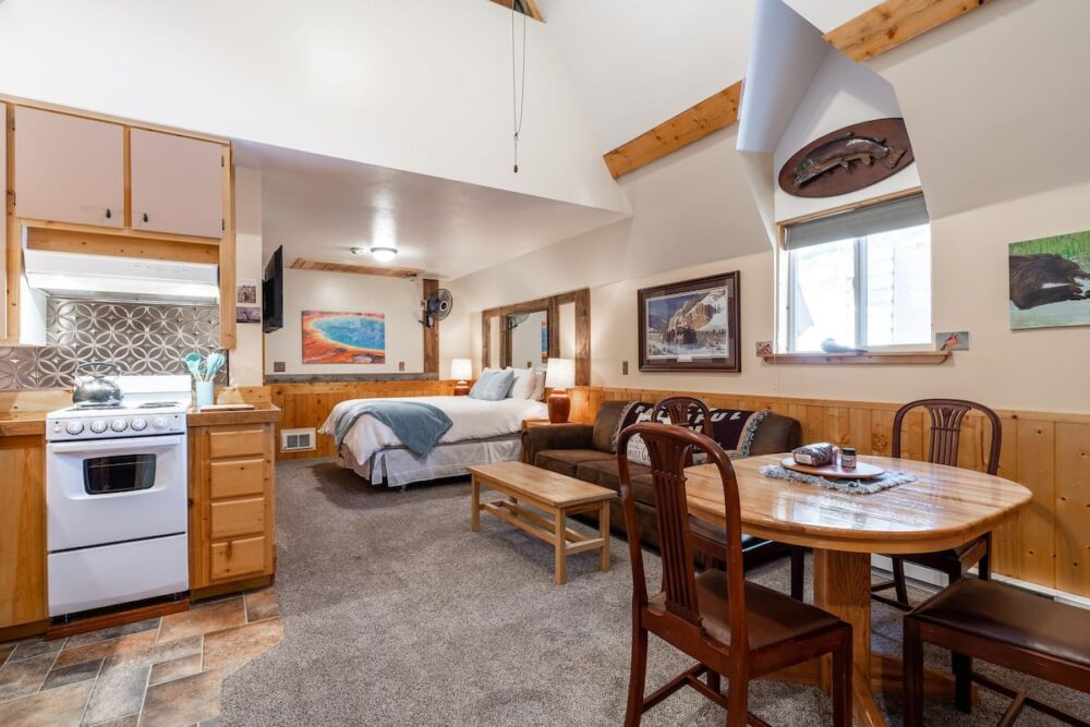 A large open plan kitchen with a bed in the distant studio area