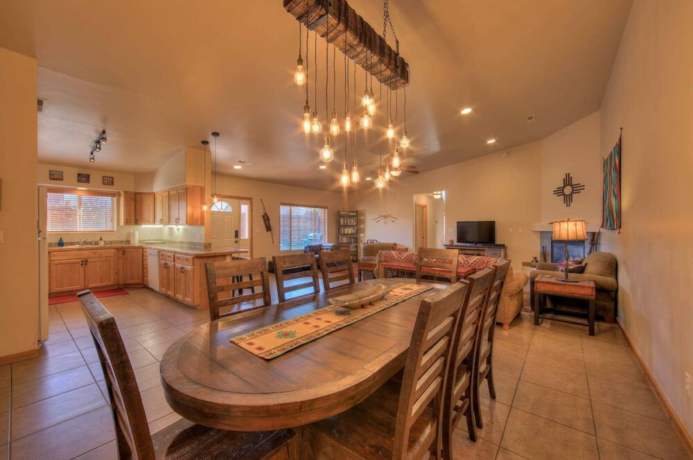 A long, rounded-edge dining table in the middle of an open floor plan kitchen, dining, living room concept, with a modern chandelier over the table.