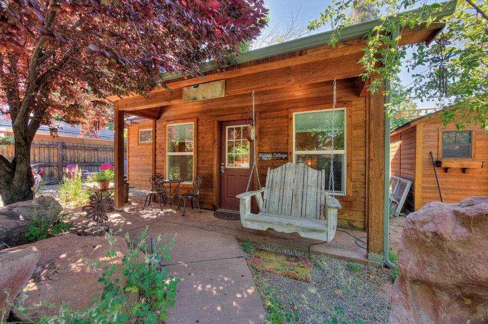A romantic, whimsical cottage surrounded by a tree and flowers, with a pastel green porch swing and a small dining table in front of the cottage in Moab.