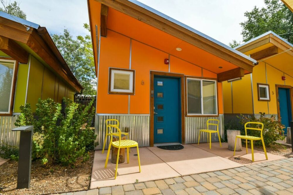 A brilliant coral pink orange house with four yellow chairs in front and a slanted tin roof, next to other colorful houses (green and yellow).