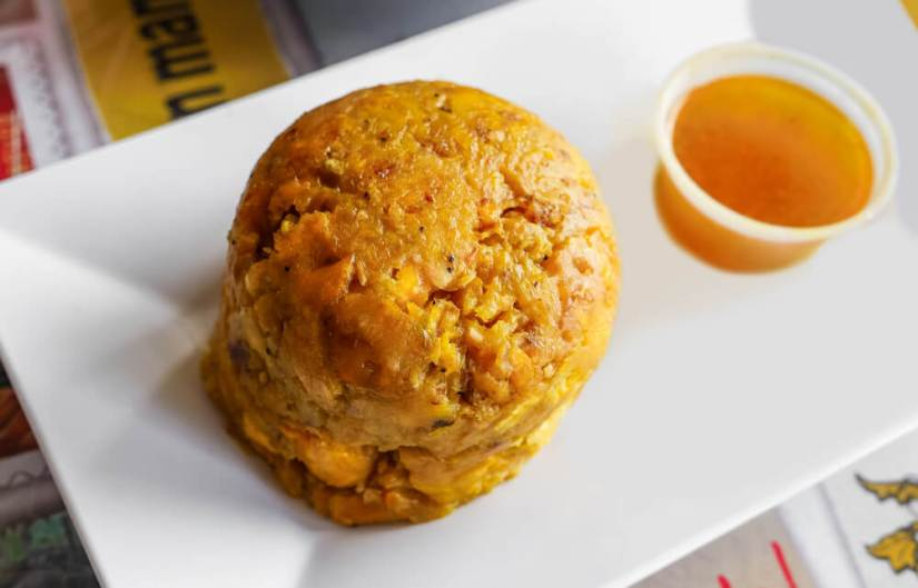 a plate of mofongo (mashed plantains) with a side of a dipping sauce