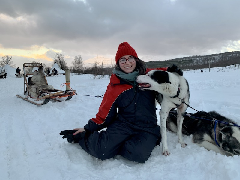 Allison posing with a friendly husky after a dog sledding tour in Tromso