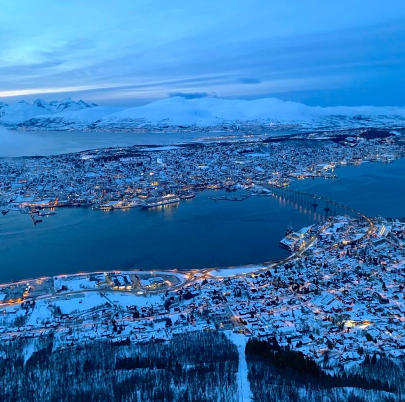views from the top of the fjellheisen cable car showing tromso lit up at night and the fjords around it
