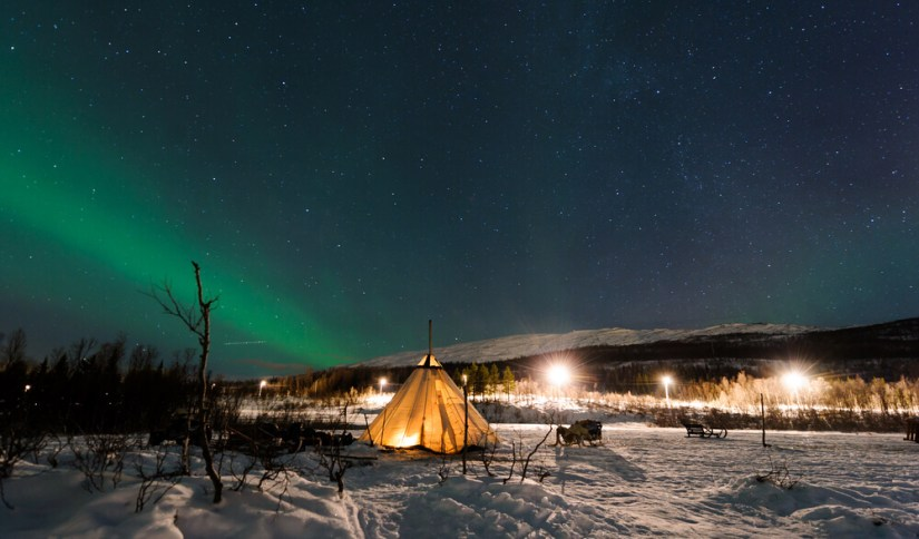 A Sami reindeer camp with an aurora over it and sleighs visible in distance