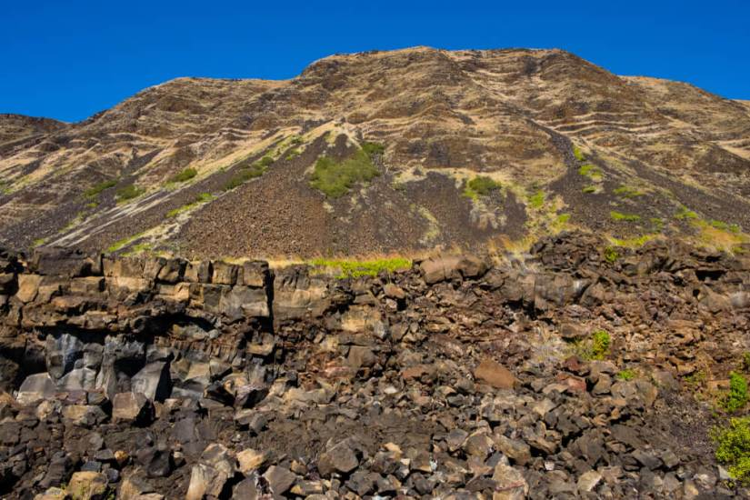 reddish brown rock with bits of green grass and vegetation on this big island hike to halape