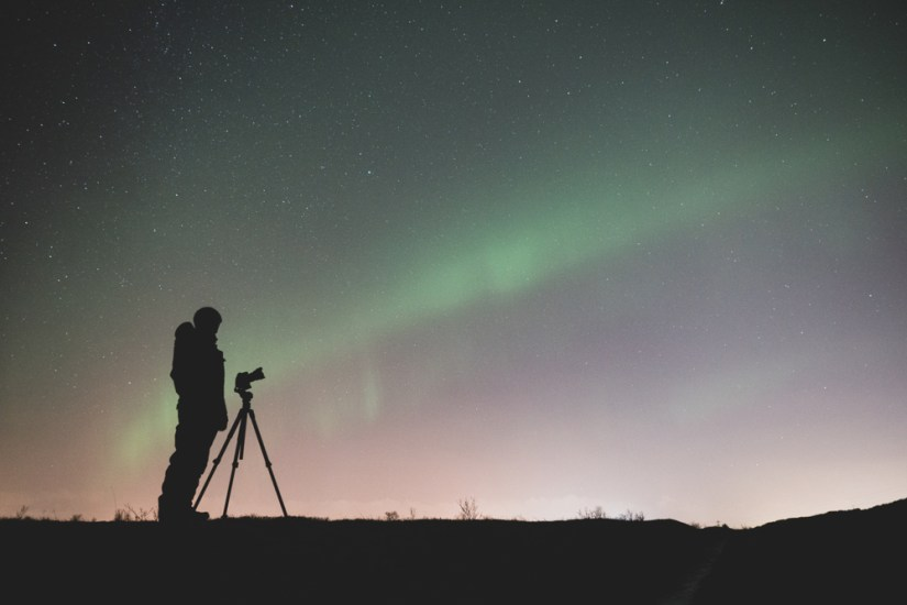 a man photographing the northern lights with a camera and a tripod with the aurora visible behind him