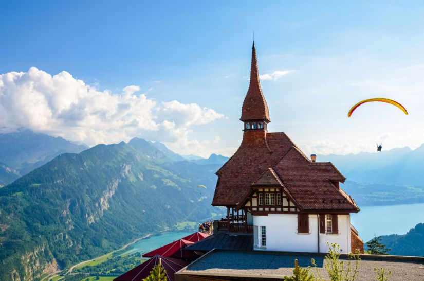 Stunning view of the top of Harder Kulm in Interlaken, Switzerland photographed in summer with paragliders flying around.