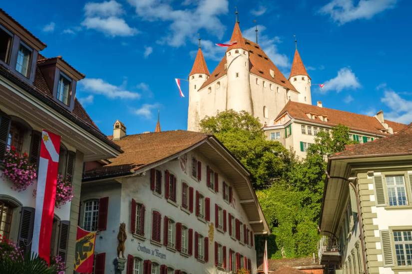 The enormous castle of Thun looming over the cute village on a sunny day.