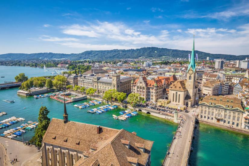 aerial view from one of the churches of zurich looking over the water and the old town of zurich and its bridges on a sunny day with a few clouds