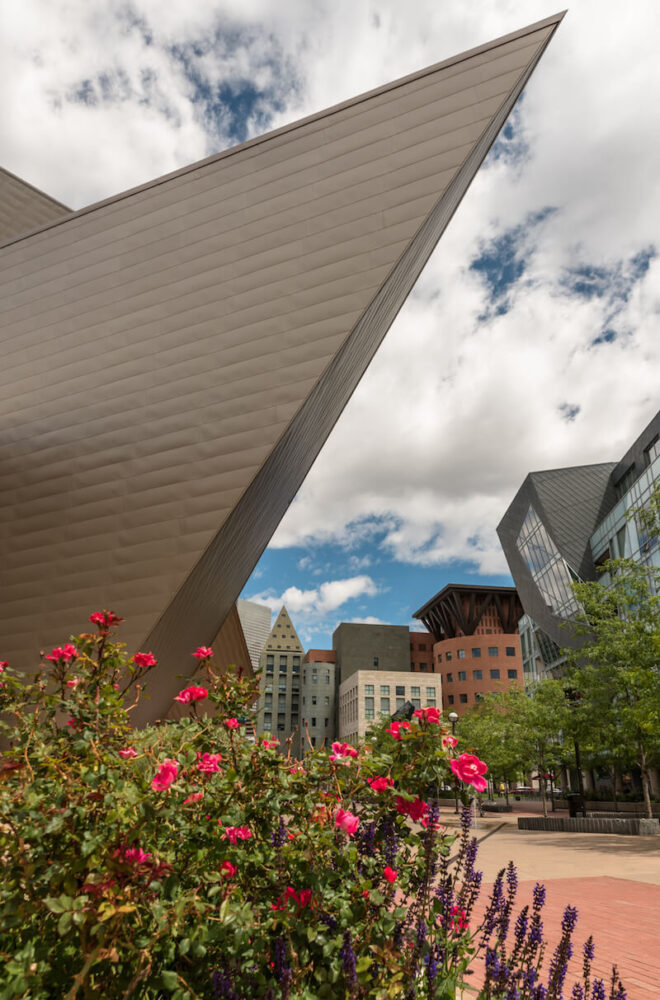 A photo of flowers in front of The Denver Art Museum with Downtown Denver in the background