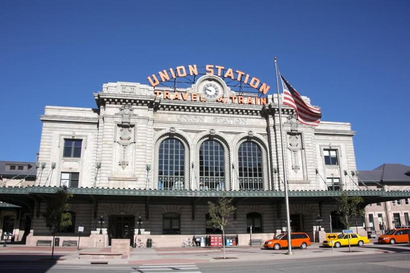 The exterior of Denver Union Station with cars and taxis in front of it