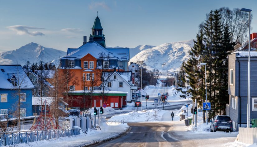 An intersection in the town of Tromso with stop lights and colorful houses and a church spire