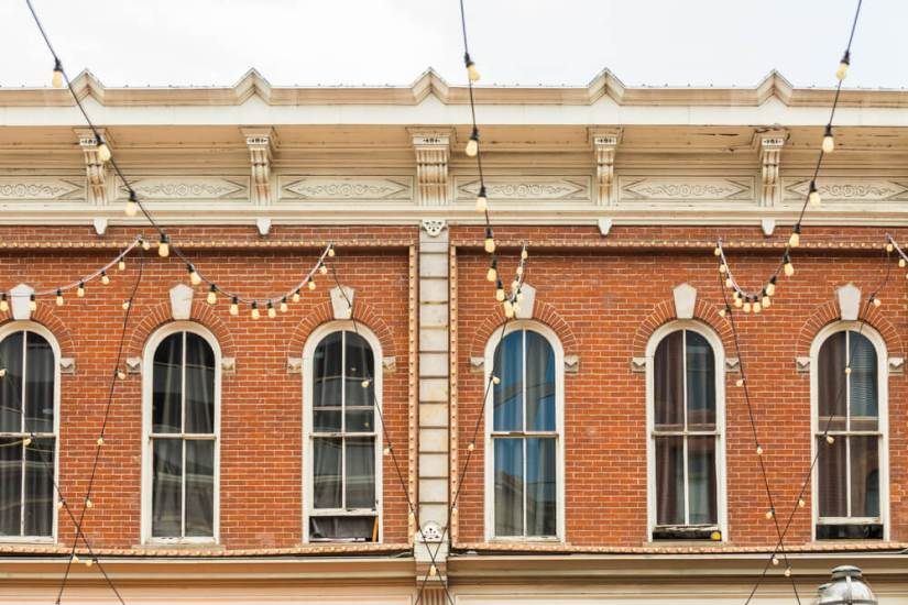 Windows of the historical brick building on Larimer Square with string lights in front of it