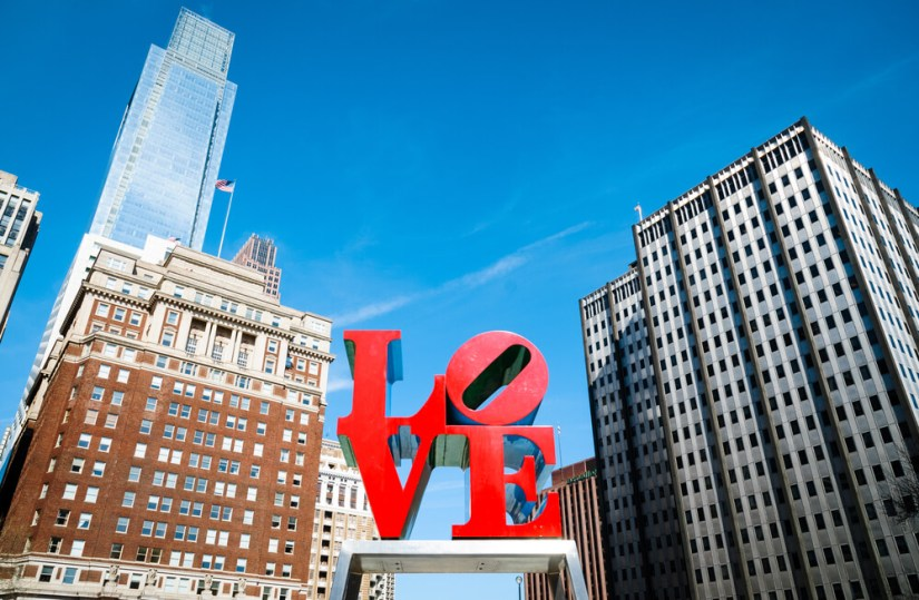 red sculpture that reads LO VE with skyscrapers around it
