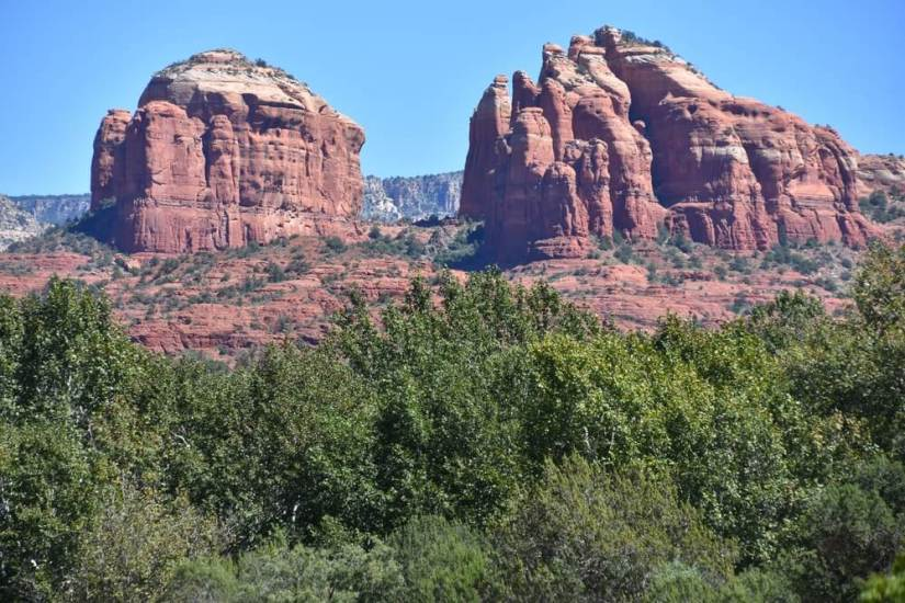 red rock formations of sedona with green trees in the foreground and two towering formations in the distance