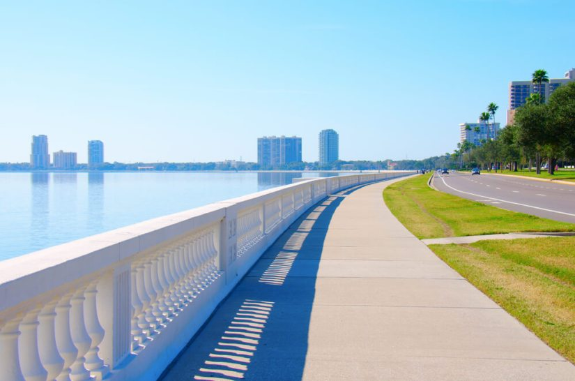 long sidewalk curved along the bay of tampa with skyscrapers in the distance