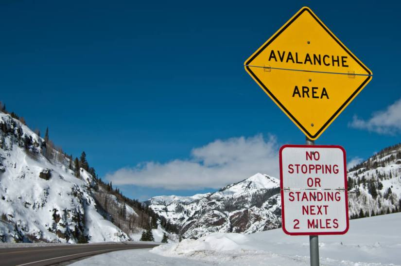"""Sign reading """"avalanche area: no stopping or standing next two miles"""" with snow in the background"""