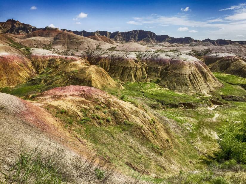 Beautiful formations within Badlands National Park with green flora and red and earth toned rock