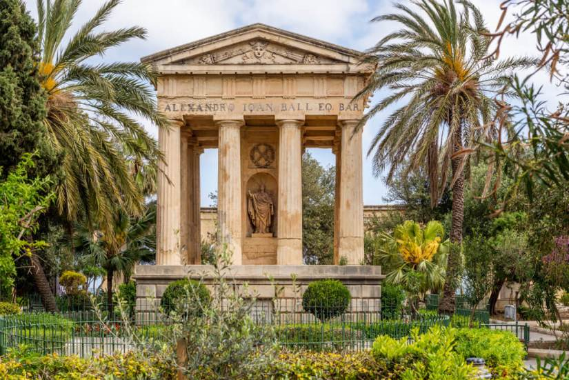 A view of a building with four pillars in Lower Barrakka Gardens surrounded by palm trees and plant life.