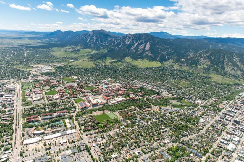 An aerial photo of Boulder Colorado with mountain and hills in the distance