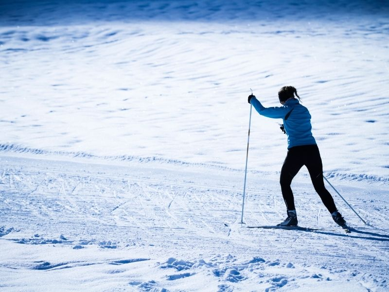 woman in a blue shirt and snow pants with cross country skis exploring in the snow