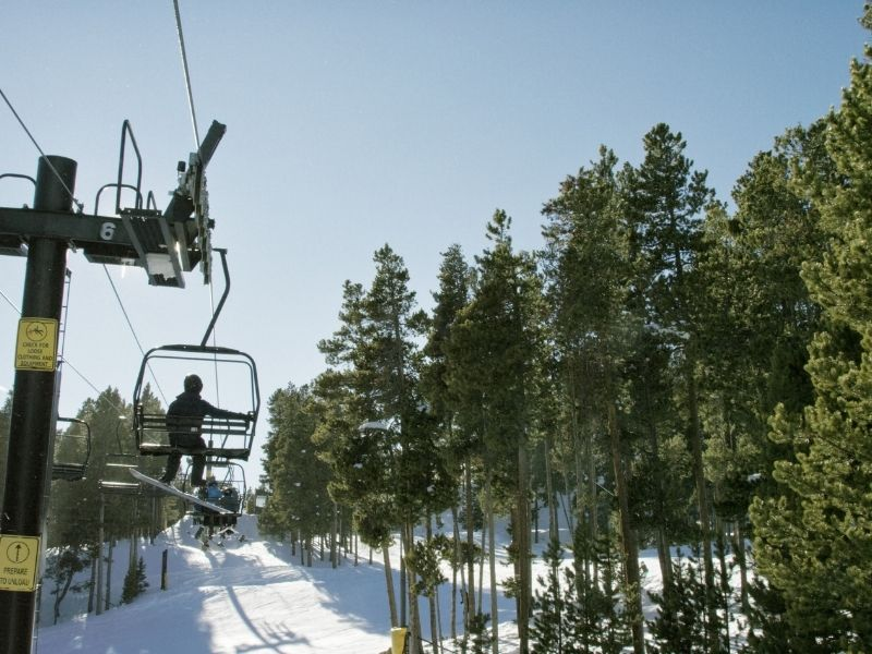 a man with a snowboard taking the chairlift up to eldora mountain resort, near boulder colorado in winter