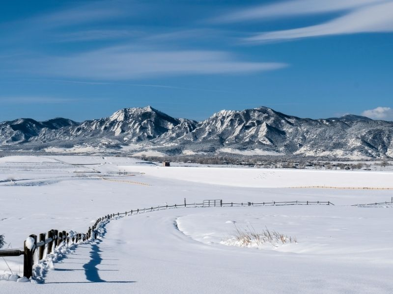 a snowy landscape in front of the flatirons section of the rocky mountains of colorado in boulder in winter