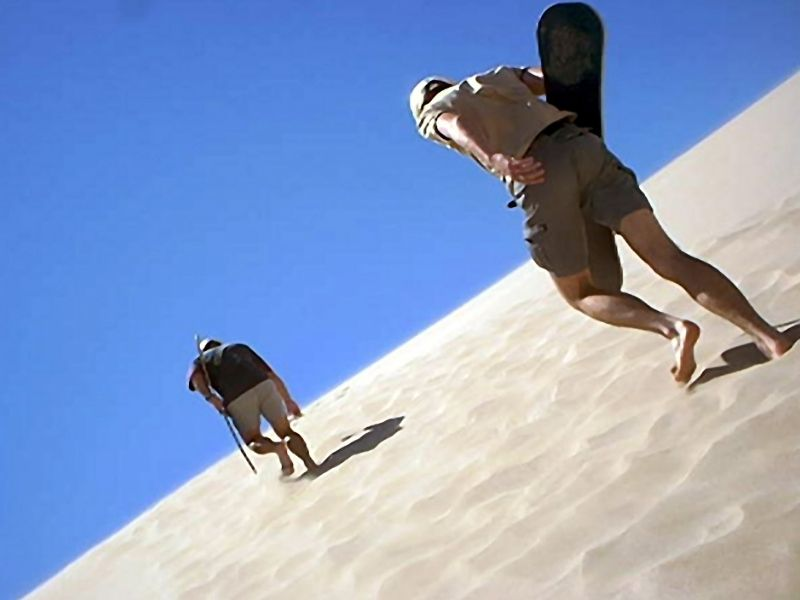 people sandboarding and walking up a sand dune