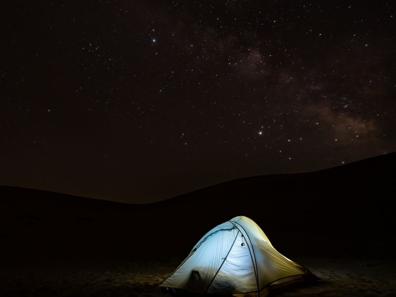 Camping in sand dunes in Colroado with stars overhead