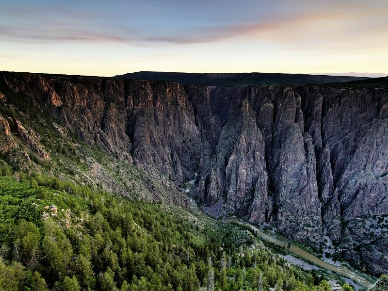 Rock formations in Black Canyon of the Gunnison National Park with a river below and lots of trees