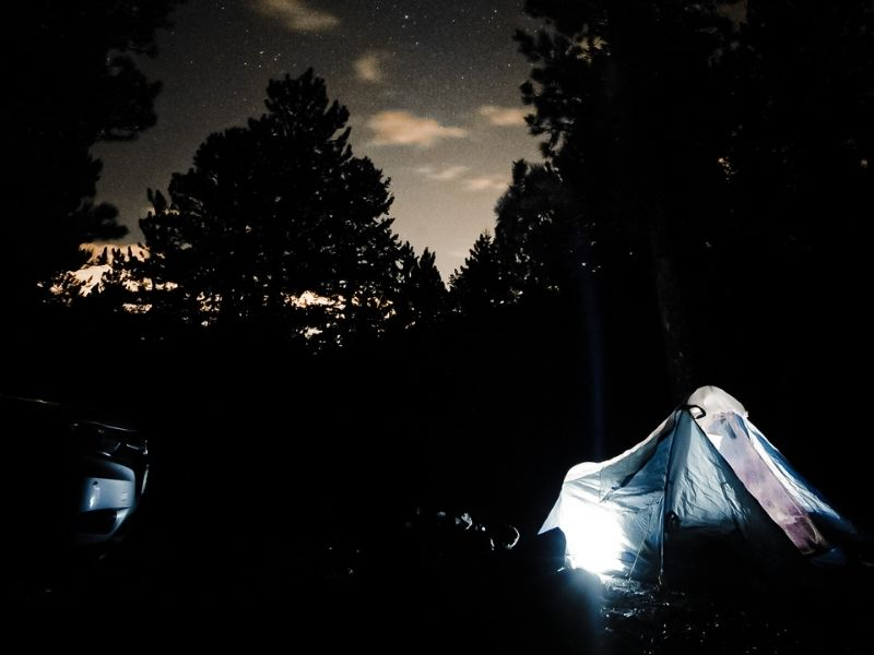 Camping tent in Colorado lit up from within with stars above in the sky