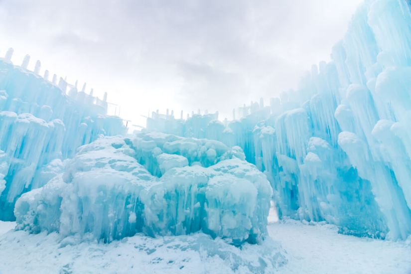 The beautiful ice formations in a brilliant turquoise pale blue color against a cloudy winter sky