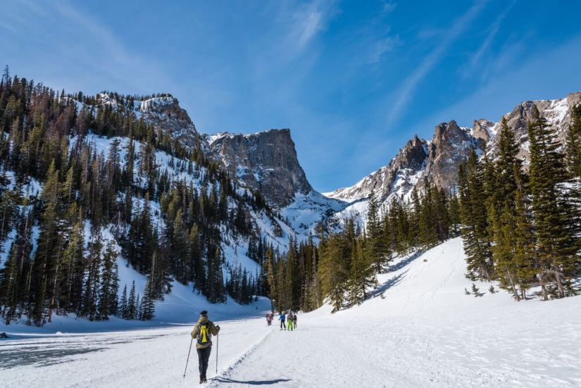 The snowy landscape of a frozen-over Dream Lake in Rocky Mountain National Park in winter in Colorado