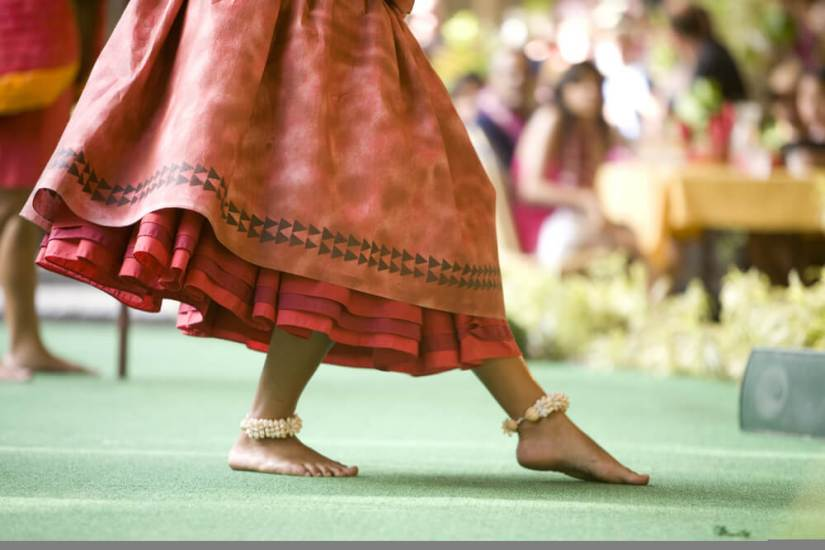 Close up of a hula dancer on a stage, focus on the her feet
