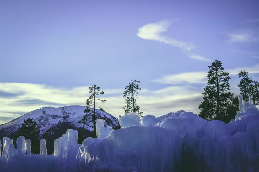 Area around the Ice Castles in Dillon with trees and mountains behind the castle formation
