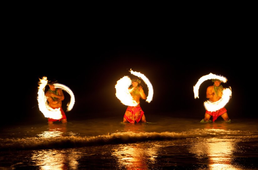 three men spinning fire at a hawaii luau
