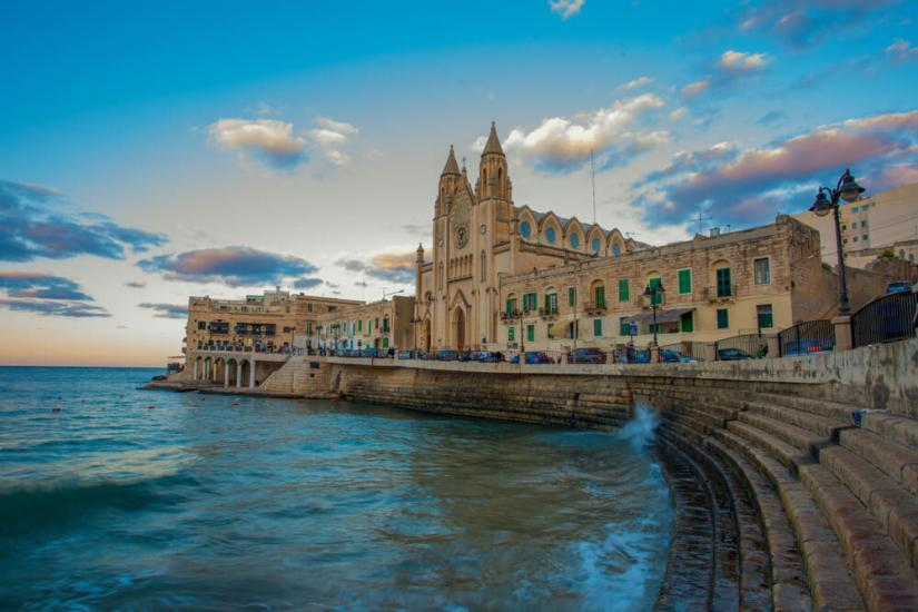 Panorama of Balluta Bay and Neo-Gothic Church of Our Lady of Mount Carmel, Balluta parish church, during evening blue hour in Saint Julien, Malta