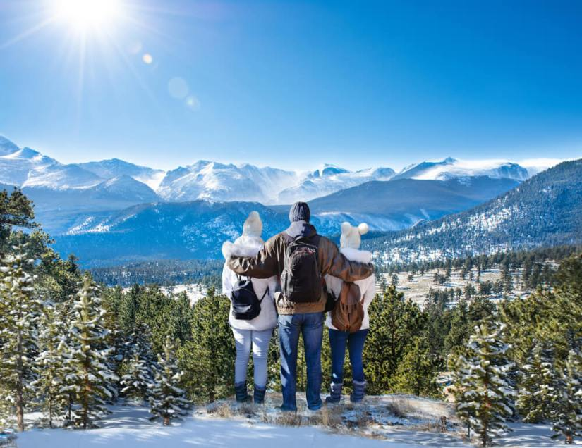 Happy family with arms around each other enjoying beautiful mountain view on winter hiking trip in Rocky Mountain National Park.
