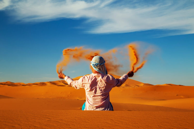 Person tossing sand while wearing a scarf around their head sitting in the orange sand of the Sahara Desert