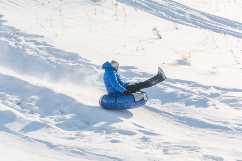Children riding on an inflatable snow tube in Rocky Mountain national park in winter