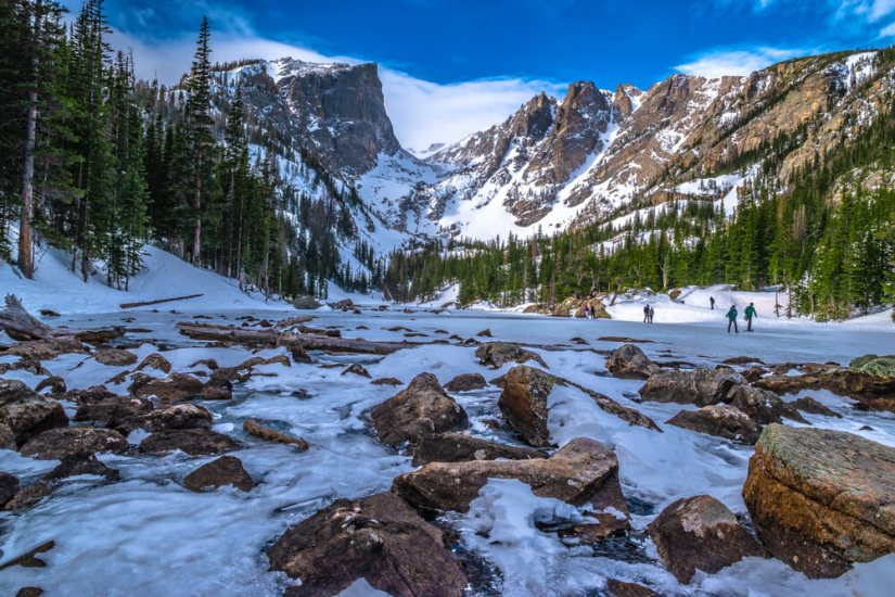 People walking on the frozen surface of Dream Lake in winter on a sunny day in Colorado