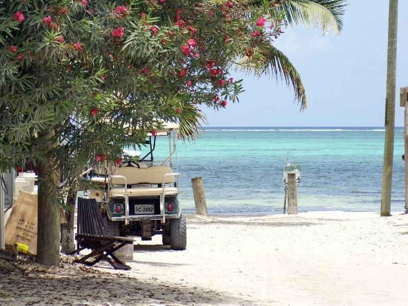 A golf cart on the sand on a beach in Belize on San Pedro
