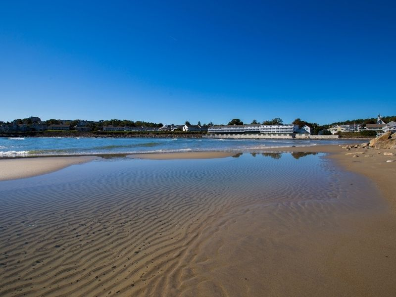 Sandy beach of Ogunquit Maine on a sunny summer day with rippled sand and water