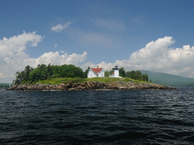 the lighthouse on curtis island as seen from the rough choppy waters out on the bay near camden maine