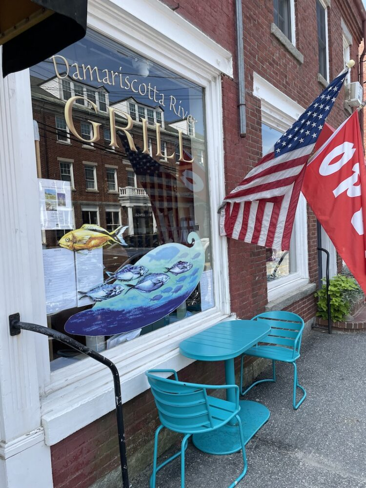 Window that says Damariscotta River Grill selling sea food, American flag and flag that says 'open