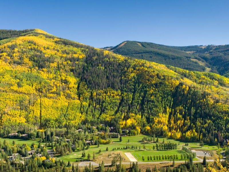 the beautiful mountain town of vail colorado with yellow aspen trees around it