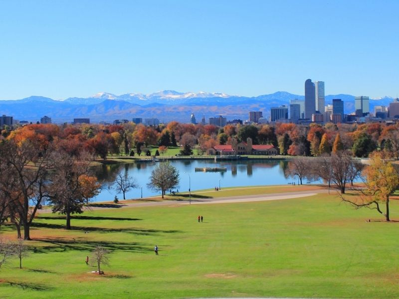 green grassy park field with colorful orange and red trees and a manmade lake in denver colorado in the fall
