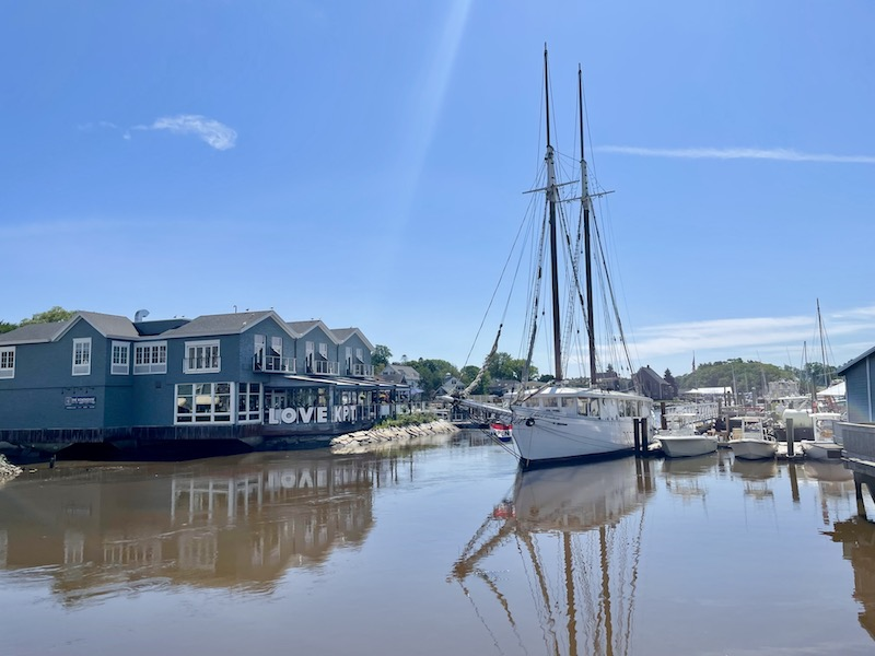 The harbor area of Kennebunkport with a large sailboat and waterfront restaurant