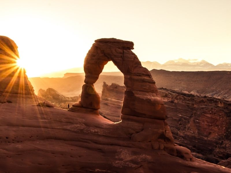Delicate Arch at sunrise with a sunburst and a small human figure at the base of the arch to give a sense of scale